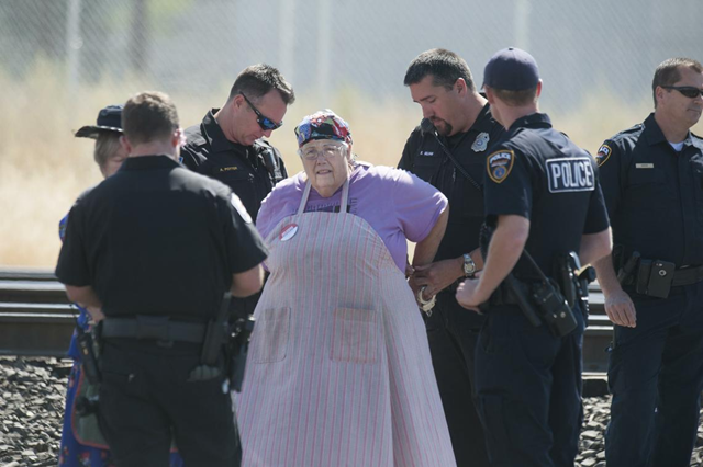 Deena Romanoff, a member of the activist group 'Raging Grannies', is arrested after she and two others blocked railroad tracks near 2302 East Trent to protest the movement of oil and coal trains through Spokane on Wednesday, 31 August 2016, in east Spokane, Washington. Photo: Tyler Tjomsland / The Spokesman-Review