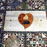 72. Floor mosaics and special paving stone. It is marked by a heart and the ducal corno (ceremonial hat) and indicates the place where the heart of Francesco Erizzo (doge from 1631 – 1646) was buried. The black shape under the corno ducal symbolises a hedgehog (riccio in Italian), the symbol of the Erizzo family. The Patriarchal Cathedral Basilica of Saint Mark. Venice. 2013