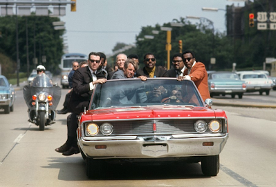 photo of Robert Kennedy with aides including former prizefighter Tony Zale and (right of Kennedy) NFL stars Lamar Lundy, Rosey Grier, and Deacon Jones in red convertible, 1968