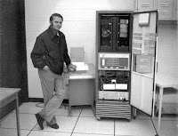 Photograph of Dave Flower standing next to a Teletype and a PDP-8