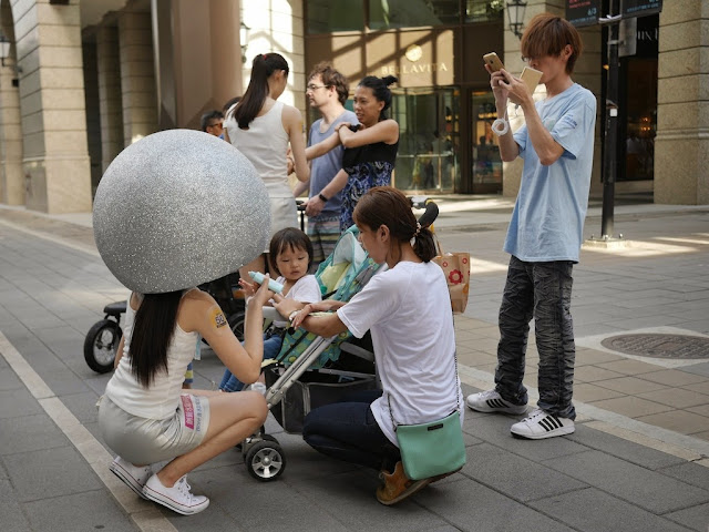 young woman wearing a huge helmet applying lotion to a toddler