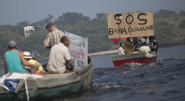 In this Sunday, 3 July 2016 photo, fishermen protest the pollution in the Guanabara bay, in Rio de Janeiro, Brazil. Rio state officials have acknowledged a real cleanup of Guanabara will take 20 years after organizers promised to do it for the Olympics, with the city still pouring at least half of its untreated sewage into its surrounding waters, including Guanabara. Photo: Silvia Izquierdo / AP Photo