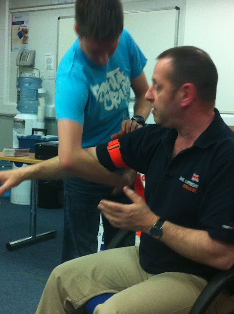 Casualty Care for Lifeboat Crew course – April 2011: crew member placing a tourniquet on our very patient trainer, Nick Darlison