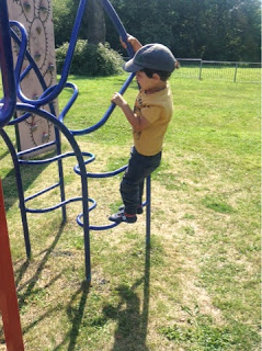 boy in yellow t shirt on climbing frame