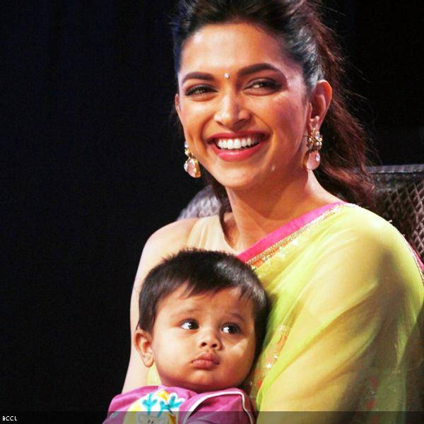 Deepika Padukone is all smiles as she poses with participant Shraddha's baby during the promotion of the movie Chennai Express, on the sets of dance reality show DID Super Moms, in Mumbai, on July 3, 2013. (Pic: Viral Bhayani)