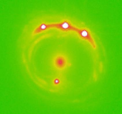 galáxia da lente gravitacional no centro e quatro quasares de fundo