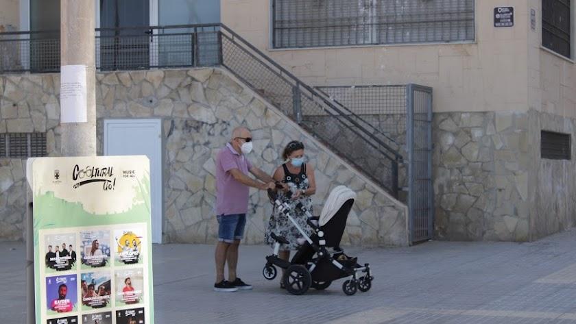 Un matrimonio con mascarilla pasea a un bebé en Almería.