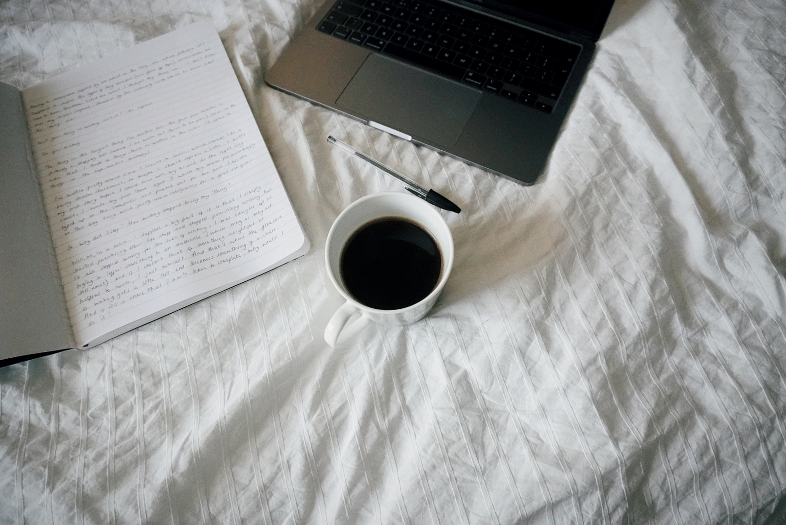the background is white bedsheets; on the sheets is a laptop, a notebook with some writing in (too small to see) and a mug of black coffee