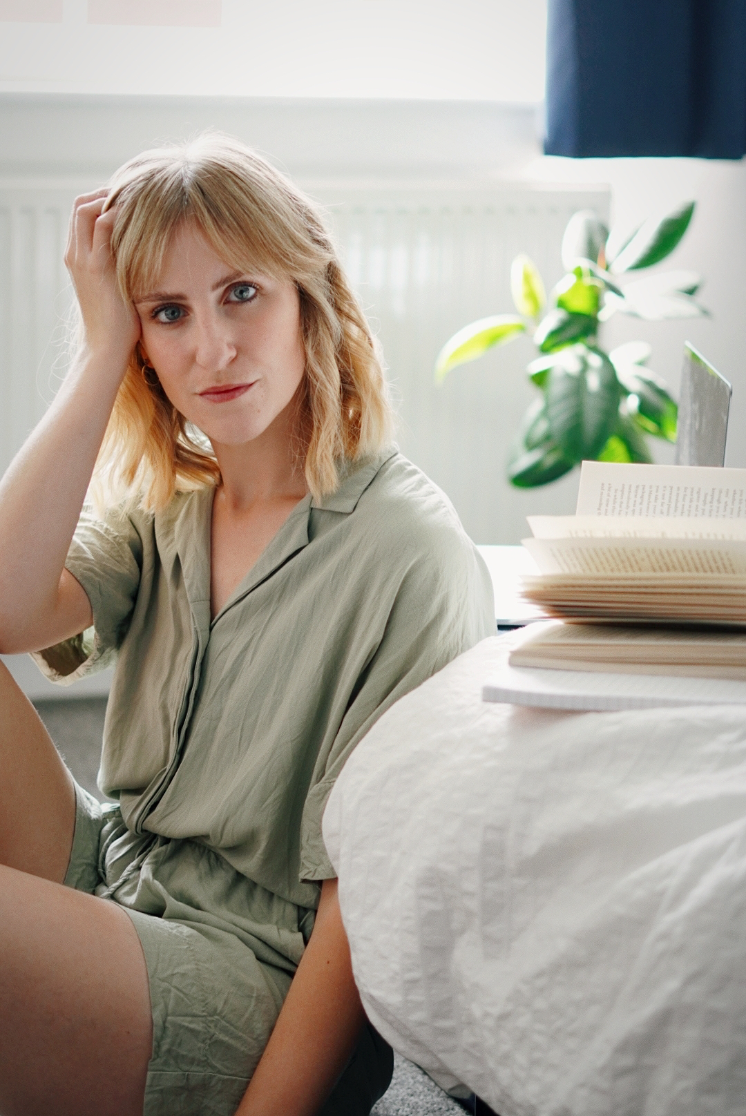 Amy is sitting on the floor next to the bed, wearing a pale green playsuit with her head resting on her hand looking to camera. Next to her are a notebook, book and laptop.