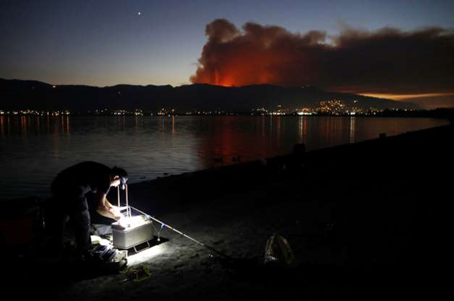 A man prepares to fish as smoke rises from the Holy Fire in Cleveland National Forest on 6 August 2018, in Lake Elsinore, California. The fast moving brush fire has burned at least 4,000 acres. Photo: Mario Tama / Getty Images