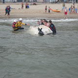 1 September 2012 - more people assist the crew members in righting the motorboat.  Photo credit: Poole RNLI/Dave Riley