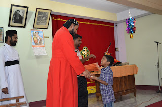 Thirumeni handing out New Year gift (a pair of pants and shirt) to each child.  Look at the eyes of this child as he is given his gift.