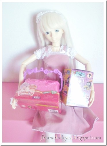 A white haired ball jointed doll (Hikaru) holding two blind boxes.  One is Lalaloopsy the other is for World's Smallest.