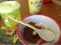 Peppa Pig bowl and spoon with pieces of chocolate egg in it.