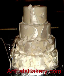 Four tier modern custom pearl swirls and white butterflies fondant wedding cake design