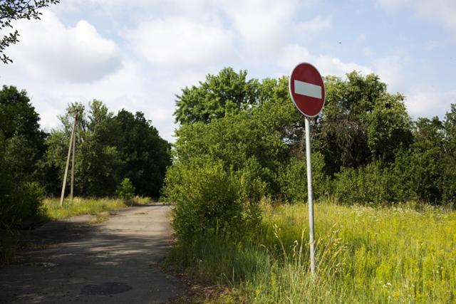 A sign in the nearly abandoned village of Karpylivka warns people not to go any further. Up ahead is a checkpoint before entering the Chernobyl exclusion zone. Photo: Anastasia Vlasova / PRI