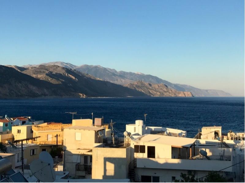 Fjellsider langs kysten i lavt sollys. Hustak i forgrunnen.