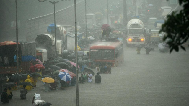 People wade along a flooded street during heavy rain showers in Mumbai on 29 August 2017. Photo: AFP