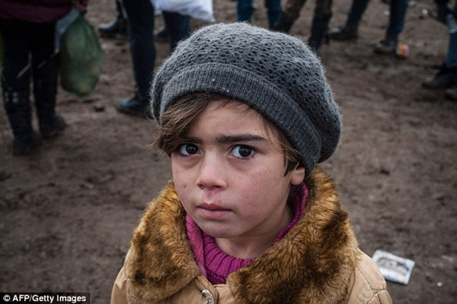 A child waits with other migrants and refugees for security check after crossing the Macedonian border into Serbia on 29 January 2016. It is not known if the boy was by himself. Photo: AFP / Getty Images