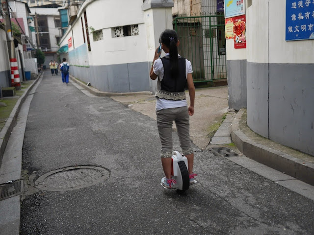 girl with a mobile phone to her ear while riding an electric unicycle down an alley