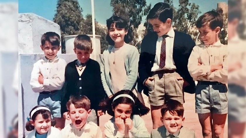 Un grupo de niños de los años 70 en un día festivo, subidos en una terrao con la Alcazaba de fondo. Iban vestidos con un rigor de adultos.