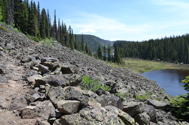 pond with Wolverine Lake in the background while climbing the rocky trail