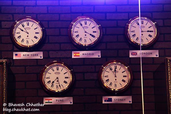 5 clocks at Toss Sports Lounge Koregaon Park showing 5 time zones — New York, Madrid, London, Pune and Sydney