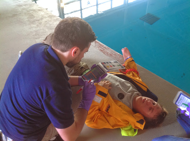 Chris checking his check cards before carrying out treatment on a severely injured casualty (Joe) - July 2014 Photo: Dave Riley