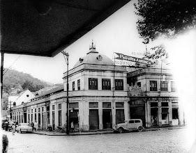 Photo: Antigo prédio do Mercado Municipal. Localizava-se aonde hoje está a Praça da Inconfidência, em frente à Igreja de Nossa Senhora do Rosário, que aliás aparece ao fundo, ainda sem torre. Foto da década de 40