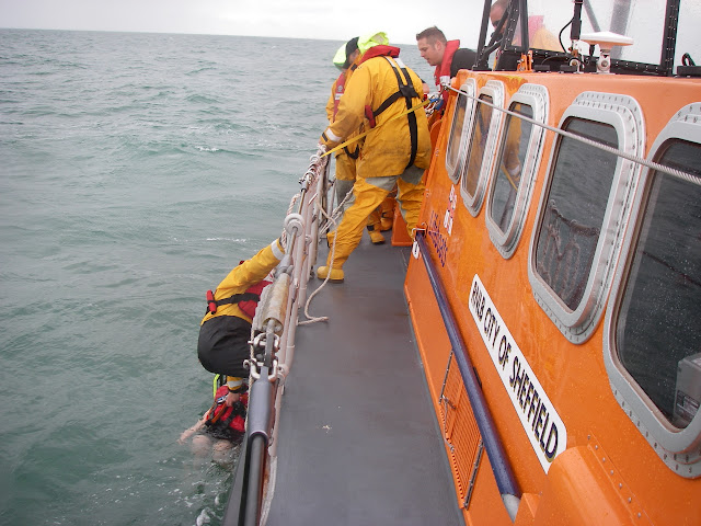 17 July 2011 – Crew Member Scott Rowland retrieving the casualty into the Jason's Cradle off Poole's all-weather lifeboat. Crew Members Simon Mumford, Emma Knight and Deputy Lifeboat Medical Adviser assisting. He was onboard in case our dummy needed medical attention! Photo: RNLI Poole/Anne Millman