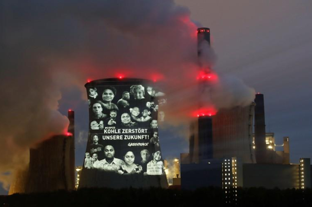 Activists of the environmental organisation Greenpeace project a slogan that reads 'No Future in Fossil Fuels' on the cooling tower of RWE coal power plant, one of Europe's biggest electricity companies in Neurath, north-west of Cologne, Germany, 10 November 2017. Photo: Wolfgang Rattay / REUTERS