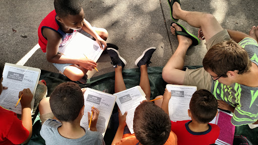 Christian helped these five boys with their Bible worksheets.