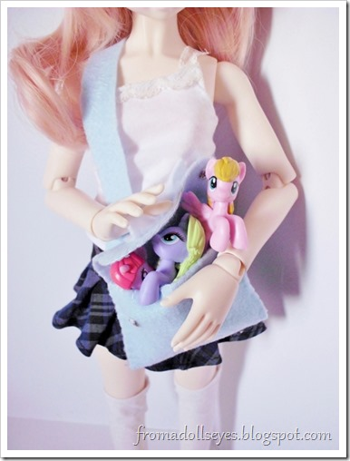 A doll trying to cram all her My Little Ponies in a bag.