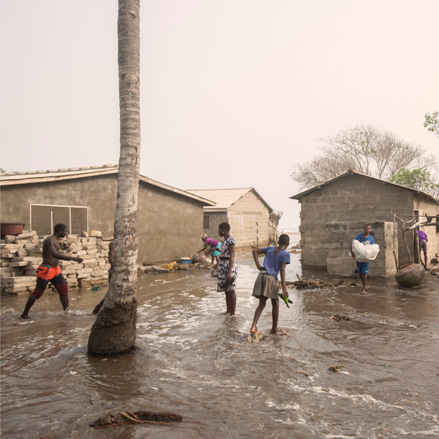People living in Fuvmeh, Ghana, walk across the village flooded by the rising sea level. Photo: Matilde Gattoni / Foreign Policy