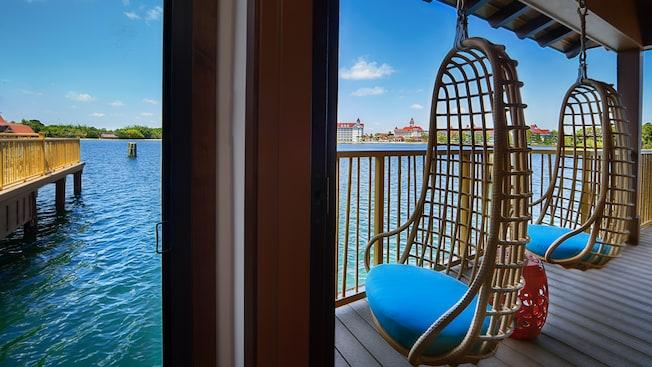 An outdoor deck featuring hanging wicker chairs while overlooking Disney's Grand Floridian Resort & Spa