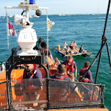 The ALB crew come alongside a home-made raft before towing its occupants to Durley Chine. 31 August 2013 Photo: RNLI Poole/Dave Riley