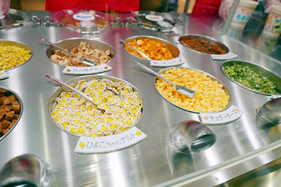 Momofuku Ando Instant Ramen Museum - select your favorite soup from among four varieties and four toppings from among 12 ingredients. Here you see corn, garlic chips, kimchee, bottom row left to right cubic roast pork, Hiyoko-chan fish sausage (the chicken face chips), cheddar cheese, and green onion