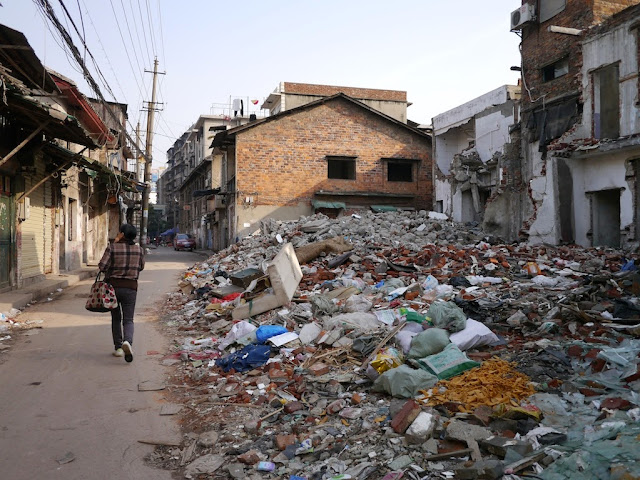 woman walking by the rubble of demolished buildings near Beizheng Street in Changsha