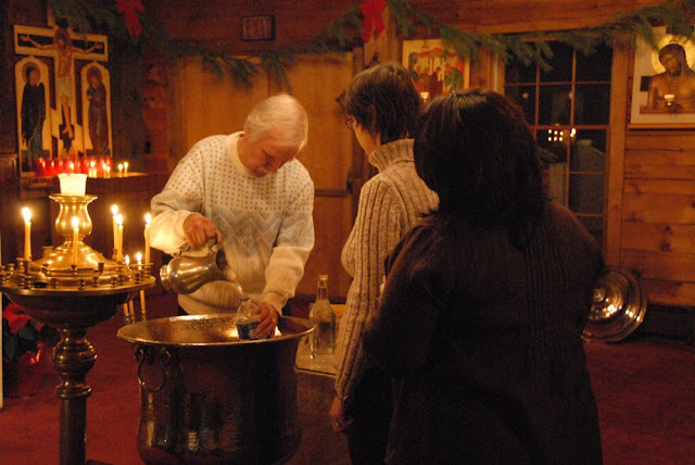 Bob assists in filling bottles with the water, so that it can be taken back to the homes of the faithful.