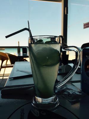 Et stort glass med sitronjuice. Havet i bakgrunnen.