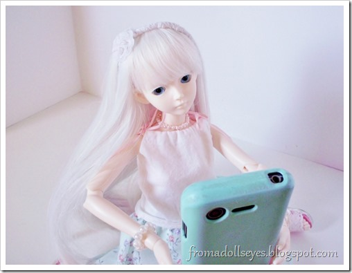 A ball jointed doll holding someone's smart phone.