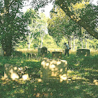 Owen weedeats around tombstones in the early morning shadows