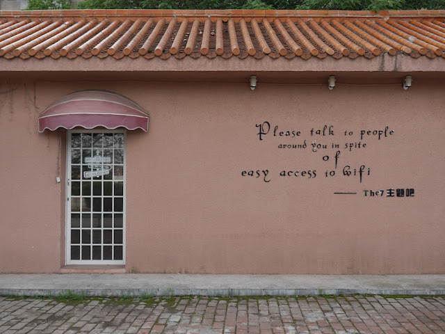 "outdoor wall of a cafe with the words ""Please talk to people around you in spite of easy access to wifi"""