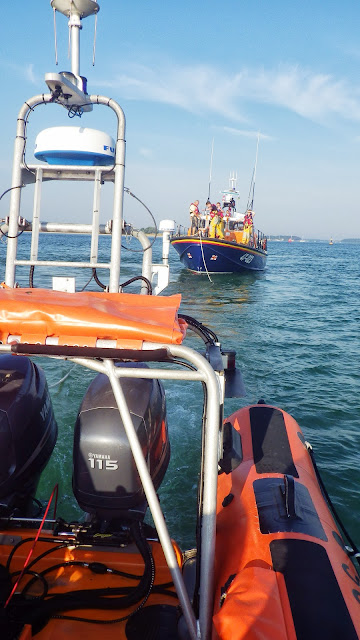Poole ILB taking the tow rope from the ALB to attach to a yacht aground on Hook Sands - 8 August 2013 Photo: RNLI/Poole