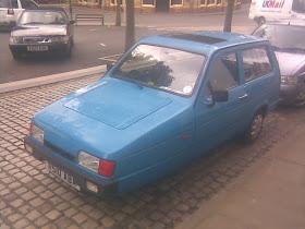 blue 3 wheel car on cobbled street