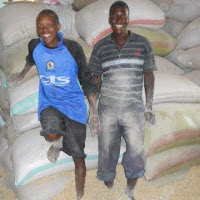 Happy servants, Michael and Moses from the church, who help fill people's sacks with maize.