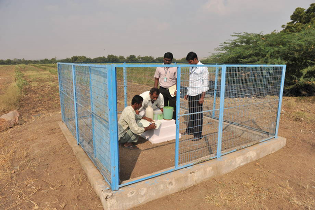 Members of an Indian farmers group measure local groundwater levels at an observation well. Photo: Noah Seelam / FAO