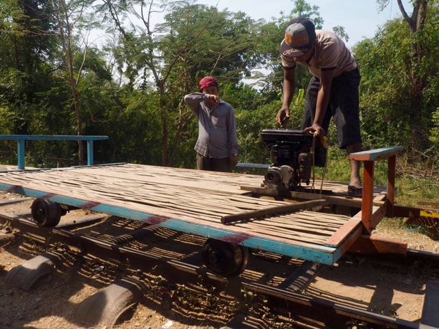 Fitting the engine into the bamboo train waiting on the tracks, in the country near Battambang, Cambodia