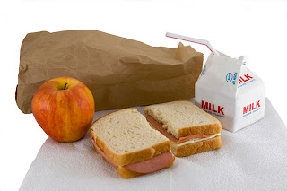 Brown paper bag and the lunch that it carried. Baloney and cheese sandwich, apple and a carton of milk. All are resting on a white napkin. Isolated background.