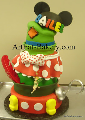 Mickey's pants and Minnie Mouse skirt, Goofy's, Peter Pan's and mouse ears hats mad hatter sweet sixteen birthday cake design with edible Captain Hook's hook, polka dot bow, and Mickey's feet.